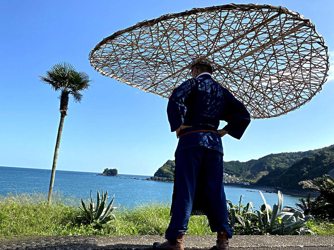 コロナウィルス感染防止帽子で海をながめる